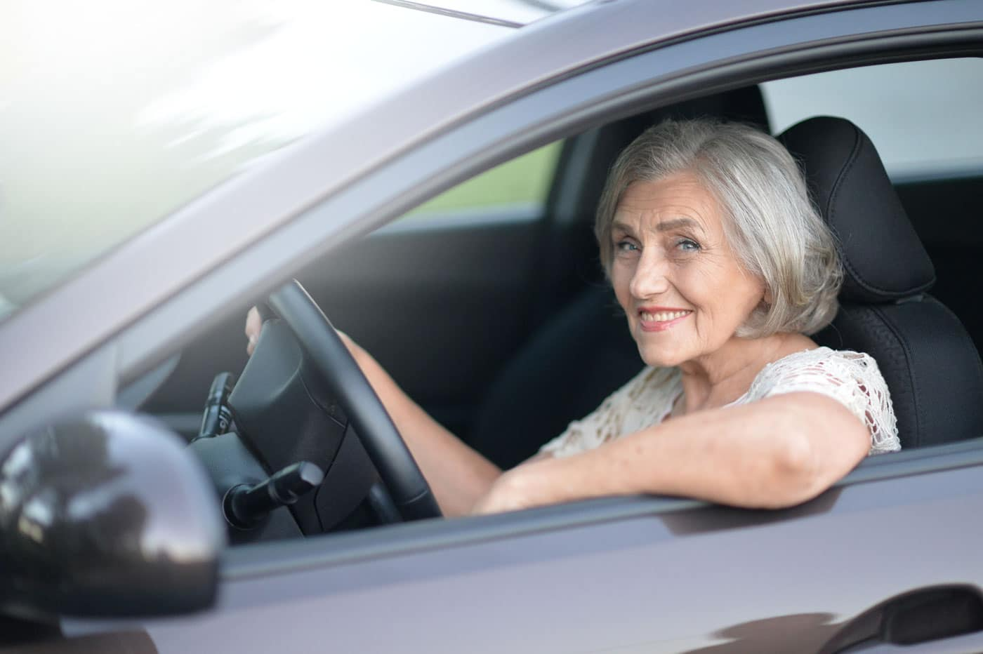 Elderly woman smiling while dirivng vehicle
